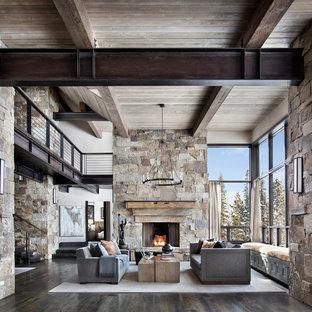 Diseño de salón para visitas abierto, moderno, grande, sin televisor, con paredes beige, suelo de madera oscura, chimenea tradicional, marco de chimenea de piedra y suelo marrón