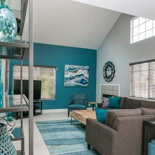 Immagine di un soggiorno contemporaneo di medie dimensioni e aperto con pareti blu, moquette, camino classico, cornice del camino piastrellata e TV autoportante