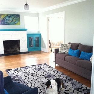 Idee per un soggiorno american style di medie dimensioni e chiuso con pareti grigie, parquet chiaro, camino classico, cornice del camino in mattoni, TV a parete e pavimento blu