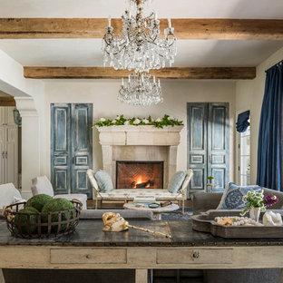 Offenes Mediterranes Wohnzimmer mit beiger Wandfarbe, dunklem Holzboden, Kamin, Kaminsims aus Stein und braunem Boden in Houston