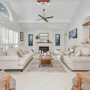 Esempio di un grande soggiorno classico aperto con angolo bar, pareti bianche, camino classico, cornice del camino piastrellata, pavimento beige e nessuna TV