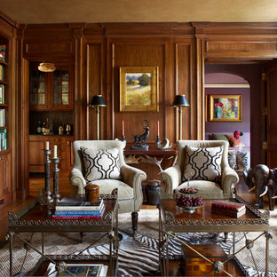 Traditional enclosed living room in New York with a library, brown walls, medium hardwood floors, a standard fireplace and a stone fireplace surround.