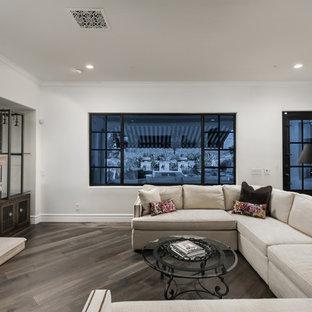 フェニックスの巨大なシャビーシック調のおしゃれなリビング (白い壁、無垢フローリング、標準型暖炉、石材の暖炉まわり、壁掛け型テレビ、茶色い床) の写真