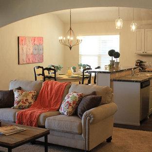 オースティンの中サイズのトラディショナルスタイルのおしゃれなLDK (ベージュの壁、カーペット敷き、標準型暖炉、石材の暖炉まわり、壁掛け型テレビ) の写真