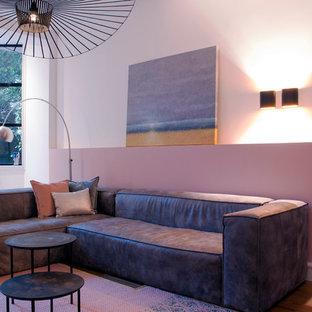 Esempio di un soggiorno minimalista di medie dimensioni e aperto con pareti rosa, parquet chiaro e TV a parete