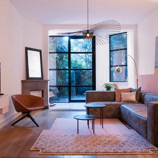 Modelo de salón abierto, minimalista, de tamaño medio, con paredes rosas, suelo de madera clara y televisor colgado en la pared