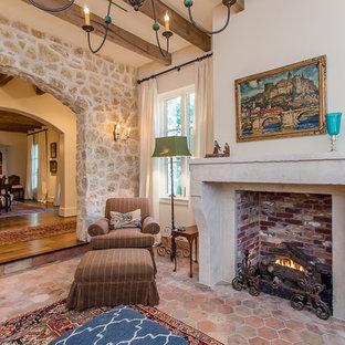ヒューストンの中サイズの地中海スタイルのおしゃれなLDK (フォーマル、ベージュの壁、テラコッタタイルの床、標準型暖炉、石材の暖炉まわり、テレビなし) の写真