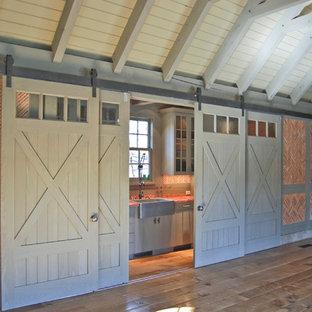 Diseño de salón abierto, tradicional, grande, sin chimenea y televisor, con parades naranjas, suelo de madera en tonos medios y suelo marrón