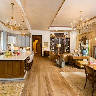 Family room - mediterranean open concept medium tone wood floor and beige floor family room idea in Houston with beige walls
