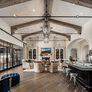 Cette photo montre un très grand salon romantique fermé avec un bar de salon, un mur blanc, un sol en bois foncé, une cheminée standard, un manteau de cheminée en pierre, un téléviseur fixé au mur et un sol marron.