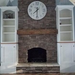 他の地域の巨大なカントリー風おしゃれなLDK (ラミネートの床、コーナー設置型暖炉、積石の暖炉まわり、茶色い床、塗装板張りの天井、塗装板張りの壁、グレーの壁) の写真