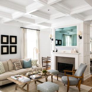 Foto de salón abierto, tradicional renovado, con paredes blancas, chimenea tradicional, marco de chimenea de piedra, suelo beige, suelo de madera clara y televisor retractable