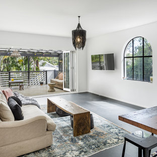 Design ideas for a mediterranean open concept family room in Sydney with white walls, a wall-mounted tv and black floor.
