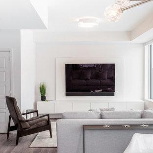 Diseño de salón minimalista, pequeño, con paredes blancas, suelo laminado y suelo marrón
