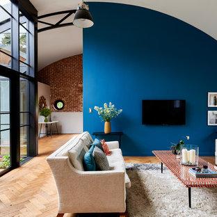 Idee per un ampio soggiorno contemporaneo aperto con pareti blu, pavimento marrone, pavimento in legno massello medio, nessun camino e TV a parete