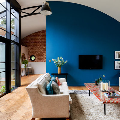 Example of a huge trendy open concept brown floor and medium tone wood floor living room design in Hampshire with blue walls, no fireplace and a wall-mounted tv