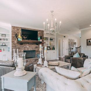 Imagen de salón para visitas cerrado, romántico, grande, con paredes grises, suelo de madera oscura, televisor colgado en la pared, chimenea tradicional, marco de chimenea de piedra y suelo marrón