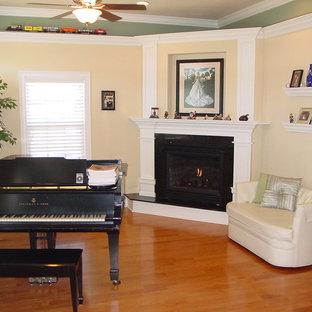 マイアミの中くらいのトラディショナルスタイルのおしゃれな独立型リビング (ミュージックルーム、マルチカラーの壁、コーナー設置型暖炉、石材の暖炉まわり、内蔵型テレビ) の写真