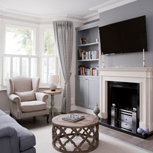 Inspiration for a small classic formal enclosed living room in Wiltshire with a standard fireplace, a stone fireplace surround, a wall mounted tv, brown floors, white walls and medium hardwood flooring.