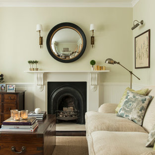 Small traditional living room in London with green walls, dark hardwood floors and a standard fireplace.