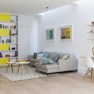 This is an example of a contemporary living room in London with white walls, light hardwood flooring, no fireplace, beige floors and a reading nook.