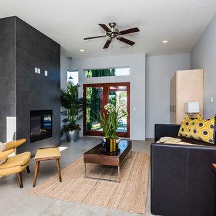 Exempel på ett modernt separat vardagsrum, med ett finrum, blå väggar, betonggolv, en bred öppen spis och en spiselkrans i trä