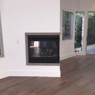 ロサンゼルスのビーチスタイルのおしゃれなLDK (淡色無垢フローリング、コーナー設置型暖炉、木材の暖炉まわり、ベージュの床) の写真