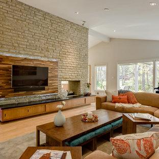Ejemplo de salón para visitas abierto, minimalista, grande, con paredes grises, suelo de madera clara, chimenea de doble cara, marco de chimenea de piedra y televisor colgado en la pared