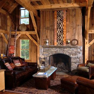 Imagen de biblioteca en casa abierta, rural, de tamaño medio, con paredes marrones, suelo de madera en tonos medios, chimenea tradicional y marco de chimenea de piedra