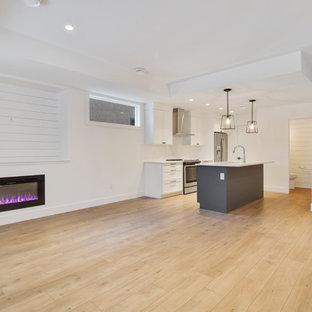 Idee per un piccolo soggiorno design aperto con pareti bianche, pavimento in laminato, camino lineare Ribbon, TV a parete e pavimento marrone