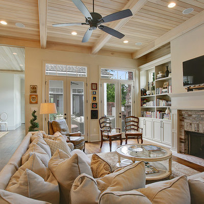 Living room - mid-sized traditional open concept dark wood floor living room idea in New Orleans with beige walls, a standard fireplace, a brick fireplace and a wall-mounted tv