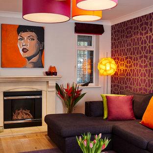 Ejemplo de salón actual con paredes púrpuras, suelo de madera clara y marco de chimenea de piedra