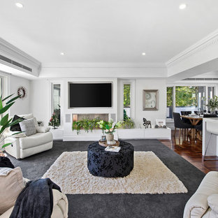 This is an example of a mid-sized contemporary open concept living room in Melbourne with white walls, carpet, a standard fireplace, a wall-mounted tv and grey floor.