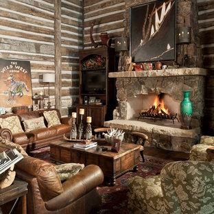 Foto de salón para visitas cerrado, rústico, de tamaño medio, sin televisor, con chimenea tradicional, marco de chimenea de piedra, paredes marrones, suelo de madera en tonos medios y suelo marrón