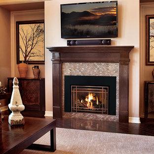 中サイズのアジアンスタイルのおしゃれなLDK (フォーマル、グレーの壁、濃色無垢フローリング、標準型暖炉、石材の暖炉まわり、壁掛け型テレビ、茶色い床) の写真