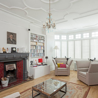This is an example of a medium sized classic living room in London with a reading nook, white walls, a metal fireplace surround, beige floors, light hardwood flooring and a standard fireplace.