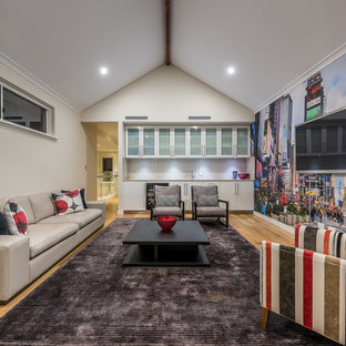 Contemporary living room in Perth with a home bar, white walls, medium hardwood floors, a wall-mounted tv and brown floor.