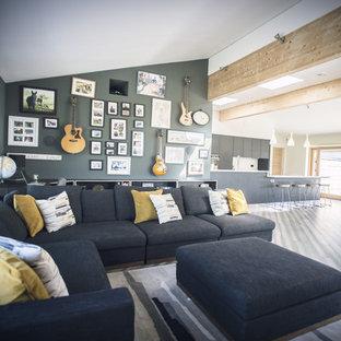 他の地域の広いコンテンポラリースタイルのおしゃれなLDK (グレーの壁、竹フローリング、薪ストーブ、漆喰の暖炉まわり、壁掛け型テレビ、グレーの床) の写真