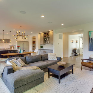 Example of a large arts and crafts open concept medium tone wood floor living room design in DC Metro with white walls, a standard fireplace, a wall-mounted tv and a tile fireplace