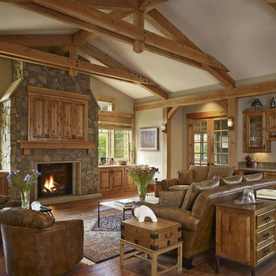 Example of a huge mountain style living room design in Denver with a standard fireplace, a stone fireplace, a concealed tv and a bar