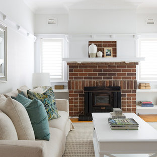 Inspiration for a small country open concept living room in Sydney with white walls, medium hardwood floors, a standard fireplace, a brick fireplace surround and brown floor.