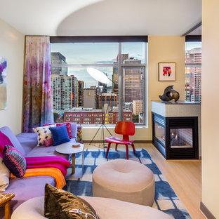 Diseño de salón abierto, contemporáneo, pequeño, con paredes amarillas, suelo de bambú, chimenea de doble cara, marco de chimenea de baldosas y/o azulejos, televisor independiente y suelo amarillo