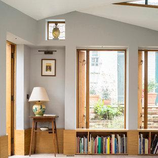 Inspiration pour un petit salon rustique fermé avec une salle de musique, un mur gris, un sol en bois clair, aucune cheminée, aucun téléviseur et boiseries.