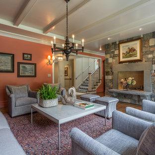 Ejemplo de salón cerrado, tradicional, grande, con suelo de madera en tonos medios, marco de chimenea de piedra, parades naranjas, chimenea tradicional y televisor colgado en la pared