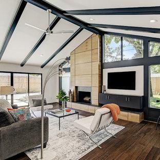 Diseño de salón abierto, retro, con paredes blancas, suelo de bambú, chimenea tradicional, marco de chimenea de madera, televisor colgado en la pared y suelo marrón