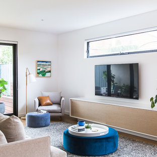 This is an example of a large contemporary formal enclosed living room in Melbourne with white walls, light hardwood floors, a wall-mounted tv and beige floor.