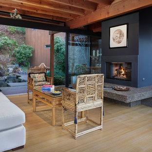 他の地域の広いアジアンスタイルのおしゃれなLDK (竹フローリング、両方向型暖炉、コンクリートの暖炉まわり、テレビなし、ベージュの床) の写真