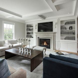 Foto de salón para visitas abierto, tradicional renovado, de tamaño medio, con paredes grises, suelo de madera clara, chimenea tradicional, marco de chimenea de piedra, televisor colgado en la pared y suelo marrón