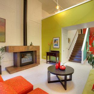 シアトルの中サイズのインダストリアルスタイルのおしゃれなLDK (緑の壁、カーペット敷き、標準型暖炉、石材の暖炉まわり、テレビなし) の写真