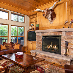 Inspiration for a medium sized enclosed living room in Boston with brown walls, medium hardwood flooring, a standard fireplace, a stone fireplace surround, a freestanding tv and brown floors.